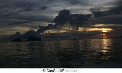 yach sailing in the sea at sunset in dark clouds
