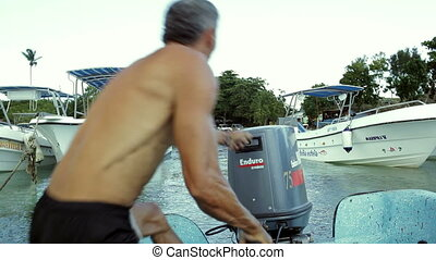 Man starting a motor of boat with several attempts - Man...