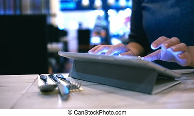 Woman typing message or e-mail on pad in cafe - Close-up...