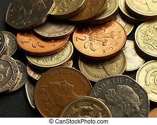 Pounds - British Pounds coins (UK currency) over a dark...