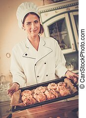 Woman cook holding homemade baked goods