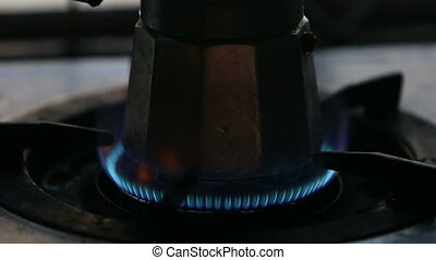 gas fire at gas-stove with coffee-pot - man hand set gas...