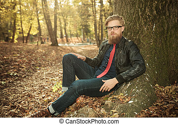 casual man wearing a leather jacket, leaning on a tree -...