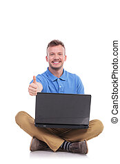 young seated man with laptop show thumb up - casual young...