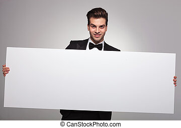 Elegant business man holding a blank board while smiling at...