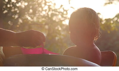 small child fed at sunrise - small blonde baby girl is fed...