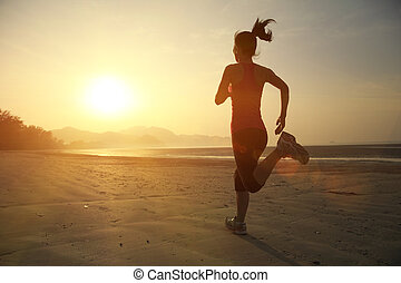 young woman jogging at beach - young fitness woman jogging...