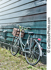 Old bicycle decorated with flowers leaning against wooden...
