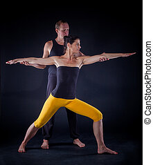 Yoga couple - Young couple doing yoga. On the black...