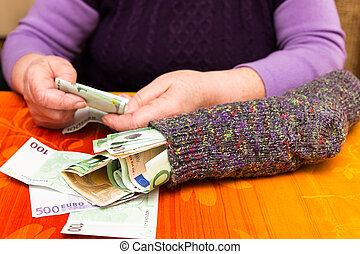 Senior adult with a sock full of money - female Senior adult...