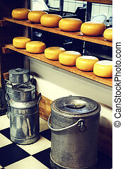 Cheese rounds and milk cans in small dairy factory. Holland