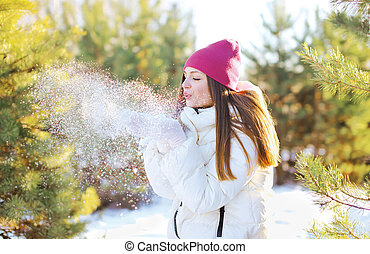 Happy woman blowing on the snow outdoors in sunny winter day