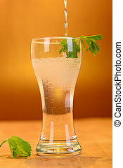 Full glass of fresh cool tonic with lime fruits isolated on back
