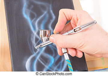 Airbrush - Hand holding a professional airbrush and painting