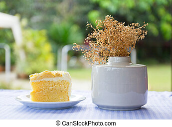 coconut cake and vase - a piece of coconut cake on plate and...