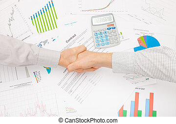 Business man working with financial data - shaking hands before signing contract