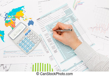 Male filling out 1040 US Tax Form with lots of financial...