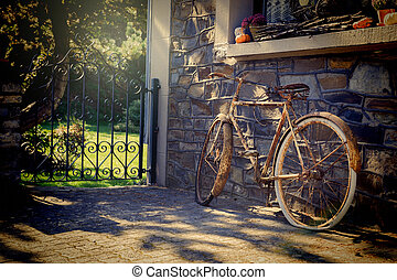 Old rusty bicycle leaning against house wall