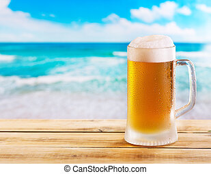 mug of beer on wooden table over sea