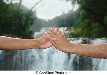 Handshake at waterfall - Handshake in front of a tropical...