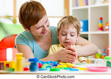 child boy and mother playing colorful clay toy - child boy...