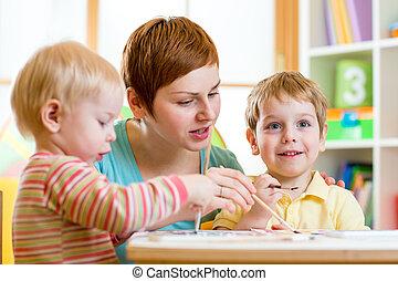 cute woman teaching kids to paint at nursery or playschool
