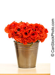 Red poppy flowers in metallic bucket on the table - isolated