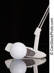 Golf putter and gold equipments on the black glass desk -...