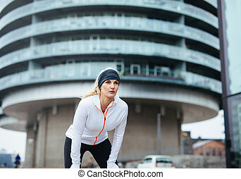 Female jogger taking a break - Young woman on sports...