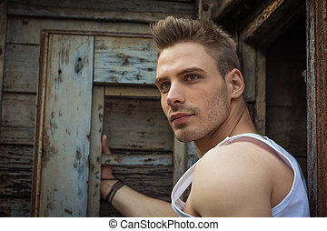 Young man against old rusty metal door and wood,...