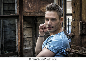 Young man sitting against old rusty train. Looking at camera