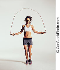 Fit young woman skipping rope. Portrait of muscular young...