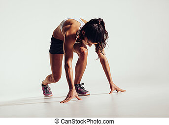 Fit female athlete ready to run over grey background. Female...