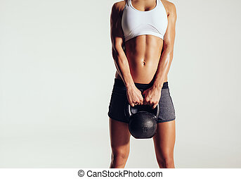 Young woman in sportswear holding a kettle bell - Cropped...