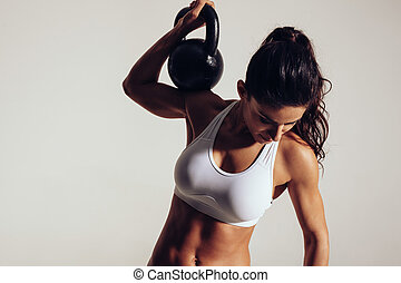 Young fitness woman exercising with kettle bell - Young...