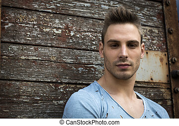 Young man portrait against old wood wall. Looking at camera