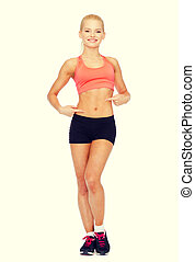 smiling sporty woman pointing at her six pack - fitness,...