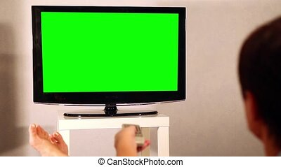 Surfing television channels TV green screen - Shot of female...