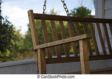 Front Porch Swing - A wooden swing hangs on an old style...