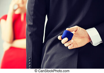 man with wedding ring and gift box - man making proposal...