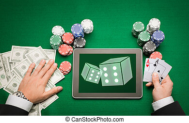 casino poker player with cards, tablet and chips