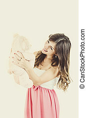 Sweet young woman holding teddy bear smiling