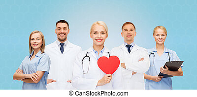 group of smiling doctors with red heart shape - medicine,...