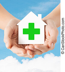 hands holding paper house with green cross - care, help,...