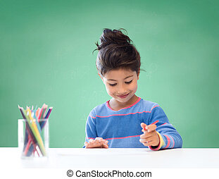 happy school girl drawing with coloring pencils - education,...