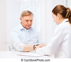 female doctor or nurse measuring blood pressure -...