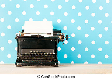 Antique black typewriter with empty paper on blue background