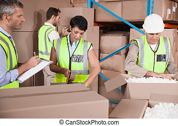 People at work in warehouse - Warehouse team working during...