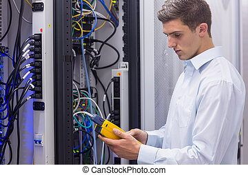 Focused technician using digital cable analyser on servers...