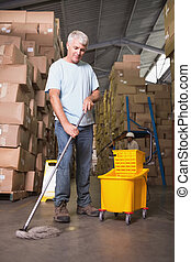 Man moping warehouse floor - Full length of man moping...